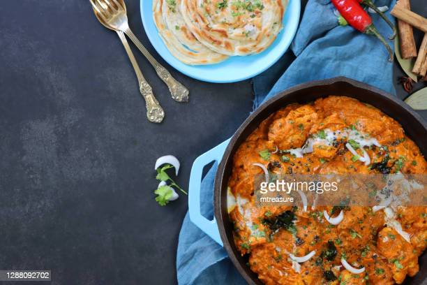 image of turquoise blue cooking pan filled with butter chicken / tikka curry, large chunks of chicken breast meat in curry sauce with garnish of red onion slices and mustard seeds, lachha paratha (layered flatbread), copy space, elevated view - indian food stock pictures, royalty-free photos & images