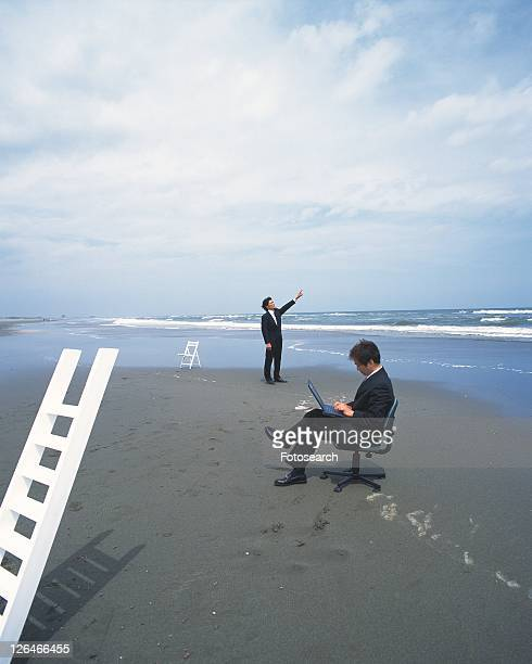 image of two businessmen at the beach, the one using a laptop, the other one pointing at the sky, far view, side view - medium group of people - fotografias e filmes do acervo