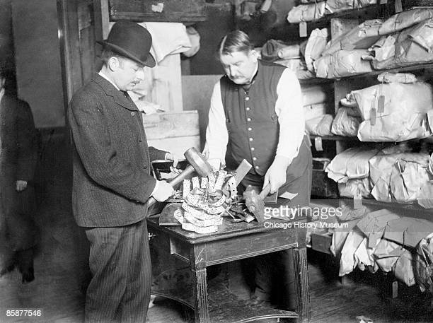 Image of two men holding hammers smashing slot machines on a table in a room with shelves of packages in Chicago Illinois 1907 The gangs made money...