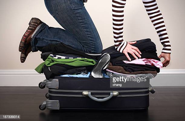 image of woman kneeing on overfilled luggage to close it - stuffing stock photos and pictures