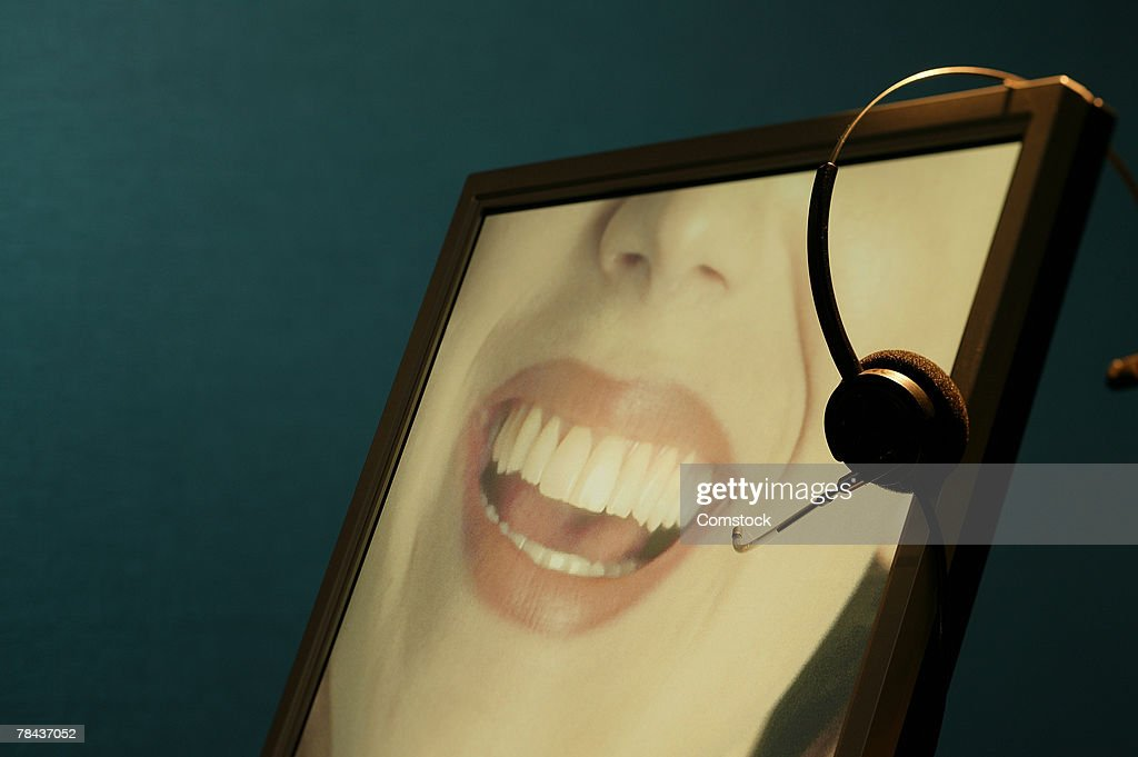 Image of woman on monitor with telemarketer's headset : Stockfoto