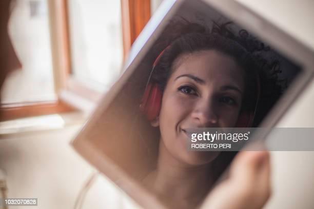 image of woman's face with headphones on digital tablet - roberto ricciuti foto e immagini stock