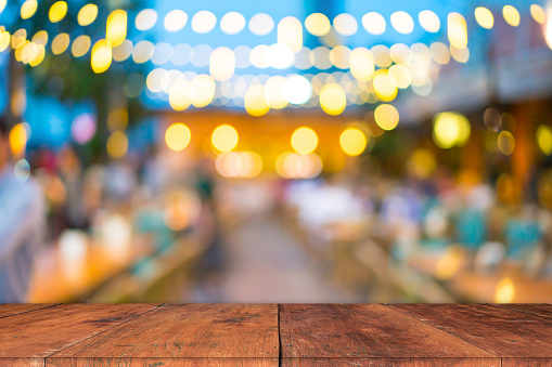 Image of wooden table in front of abstract blurred restaurant lights background. - gettyimageskorea