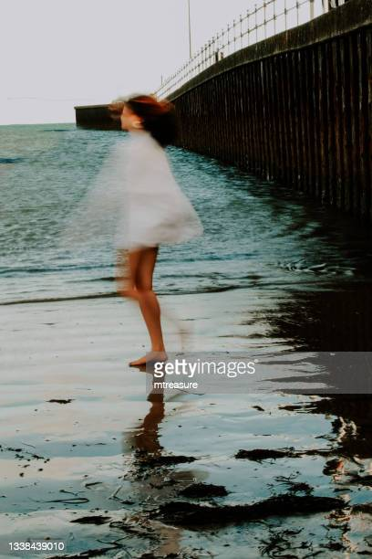 image of young woman walking barefoot on beach at water's edge, paddling low tide by pier, blurred motion, weymouth, dorset, england, uk - human leg stock pictures, royalty-free photos & images
