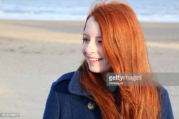 Image portrait of smiling red haired teenage girl, beach background