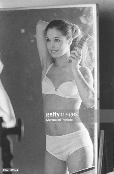 Image reflected by the mirror of the Italian dancer Oriella Dorella in bra and panties while she is brushing her hair in the dressing room of the...