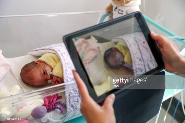 Image released on May 27 A nurse makes a video of a newborn baby in the maternity ward at Frimley Park Hospital in Surrey to send to the parents as...