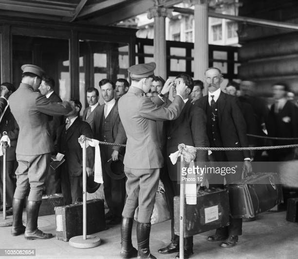 Image shows a health inspection taking place for new immigrants entering the United States. Photograph taken at Ellis Island, New York, 1920.
