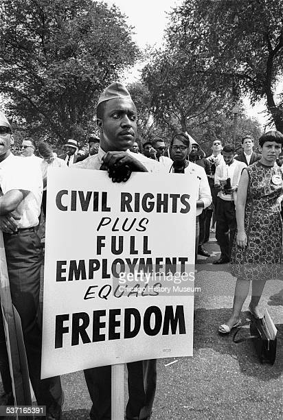 Image shows a man carrying a sign that reads 'Civil Rights Plus Full Employment Equals Freedom' at the March on Washington for Jobs and Freedom in...