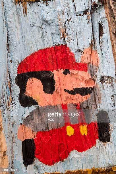 Image shows a painting of Super Mario on a tree hole at Jinhai Road Campus Shanghai Second Polytechnic University on September 7 2016 in Shanghai...