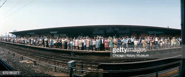 Image shows a panoramic view of a crowd standing by the tracks at a train station watching the Robert F Kennedy funeral train June 8 1968 The Senator...