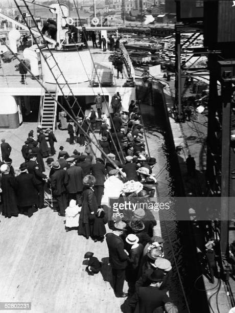 Image shows passengers and immigrants on the B and C decks towards the aft of the White Star liner RMS Olympic as she sits in port and they await...
