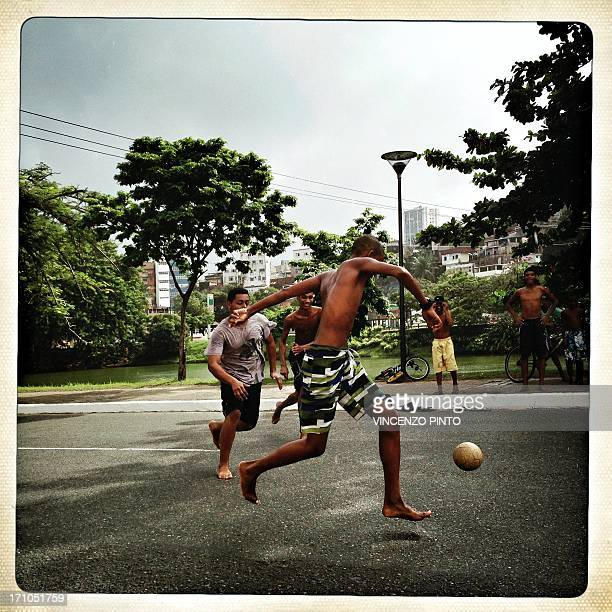 Image taken with a mobile phone showing boys playing street football during the FIFA Confederations Cup Brazil 2013 in Salvador de Bahia on June 20...