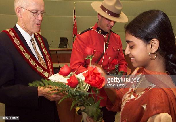 IMAGEIn return for a citizenship Markham Mayor Donald Cousens recieves a rose from Vythegi Srithayakumar who has lived in Canada for five years Her...