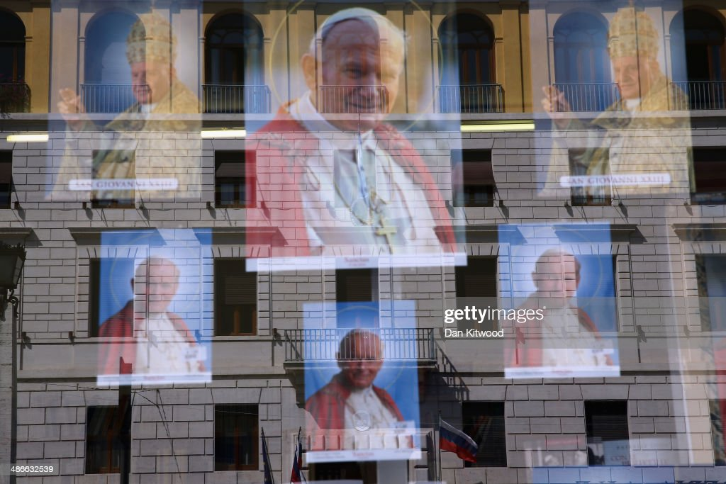 Images depicting the late Pope John Paul II and Pope John XXIII hang in a shop window near St Peter's basilica on April 25, 2014 in Vatican City, Vatican. The late Pope John Paul II and Pope John XXIII will be canonised on Sunday 27 April, inside the Vatican when 800,000 pilgrims from around the world are expected to attend.
