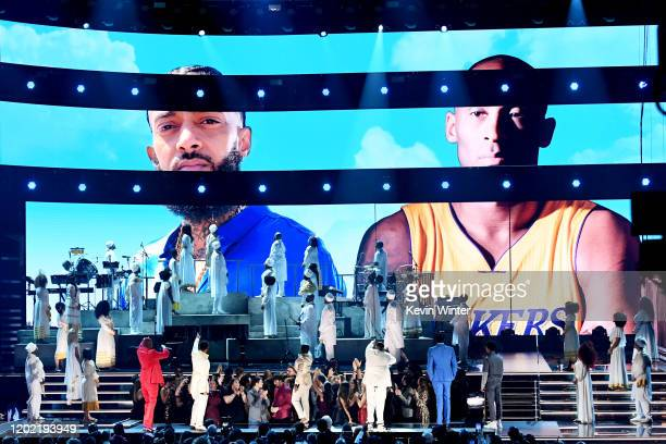 Images for the late Nipsey Hussle and Kobe Bryant are projected onto a screen while YG John Legend Kirk Franklin DJ Khaled Meek Mill and Roddy Ricch...
