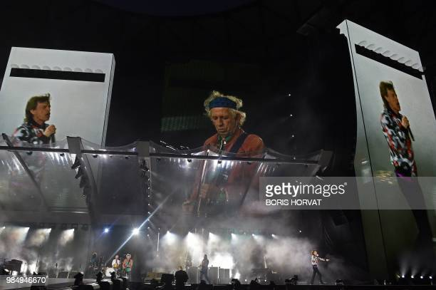 Images of British musicians Mick Jagger and Keith Richards of The Rolling Stones are projected onto screens as the band performs during a concert at...