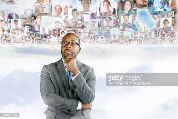 Images of business people floating above African American businessman's head