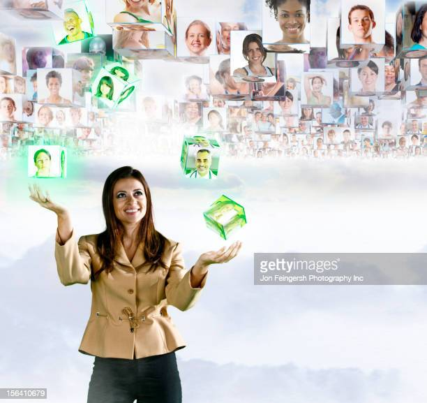 Images of business people floating over head of Hispanic businesswoman
