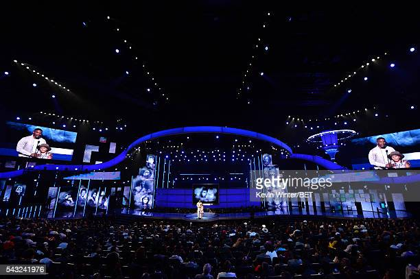 Images of late boxer Muhammad Ali are projected onto screens over the stage while actor Jamie Foxx and daughter Annalise Bishop speak onstage during...