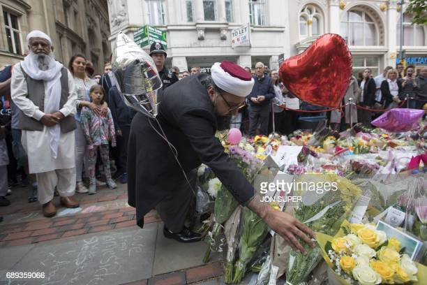 Imam Irfan Chishti lays flowers for the victims of the Manchester bombing as multifaith leaders visit St Ann's square in Manchester on May 28 2017 A...
