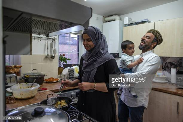 Imam Raza Ahmed holds his son Daud as his wife Anam prepares food for iftar at their family home on May 08 2020 in London England Ramadan is the...