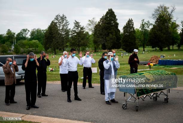 Imam Said Sherzadi leads close family in prayer near the casket of Ghulam Merzazada at the National Memorial park cemetery in Fairfax Virginia on May...