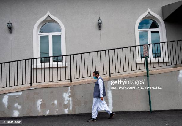 Imam Said Sherzadi walks past the Mustafa Center mosque as he goes to lead a funeral in Fairfax Virginia on May 14 2020 Due to the COVID19 pandemic...