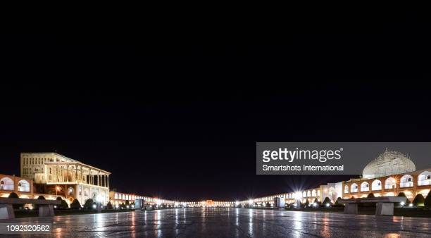 Imam Square illuminated at night with Sheikh Lotfollah mosque on the right and Ali Qapu palace on the left in Isfahan, Iran