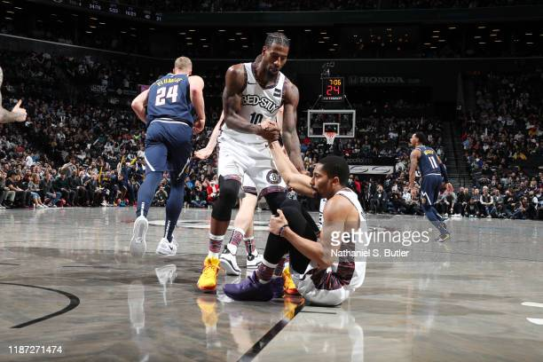 Iman Shumpert of the Brooklyn Nets helps Spencer Dinwiddie of the Brooklyn Nets off the floor during a game against the Denver Nuggets on December 8...