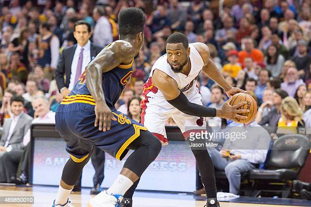 Iman Shumpert of the Cleveland Cavaliers guards Dwyane Wade of the Miami Heat during the first half at Quicken Loans Arena on April 2 2015 in...
