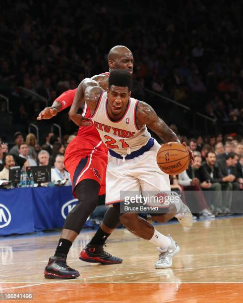 Iman Shumpert of the New York Knicks is fouled by Johan Petro of the Atlanta Hawks in the fourth quarter at Madison Square Garden on April 17 2013 in...