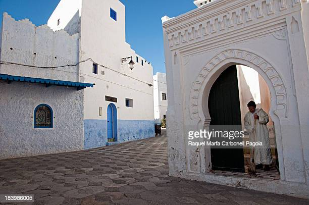 Iman sweeping mosque entrace in Asilah medina, Morocco. 2013