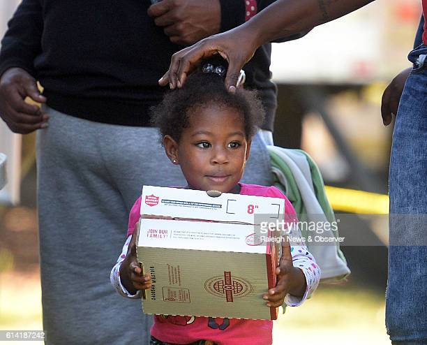 Imani Keith carries free pizzas as a Papa John's mobile pizza kitchen serves free pizzas to flood victims on Oct 12 2016 in Goldsboro NC The truck...