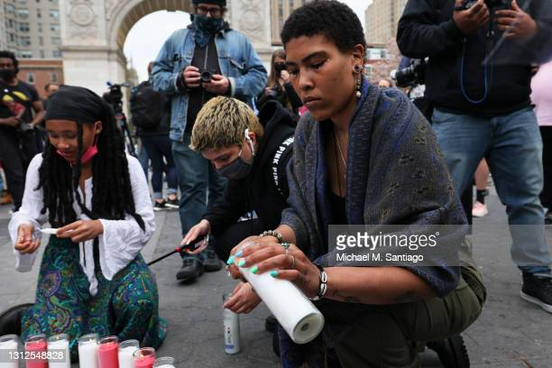 Imani, who chose not to disclose a last name, lights a candle at a makeshift memorial during a vigil for Daunte Wright and Dominique Lucious at...