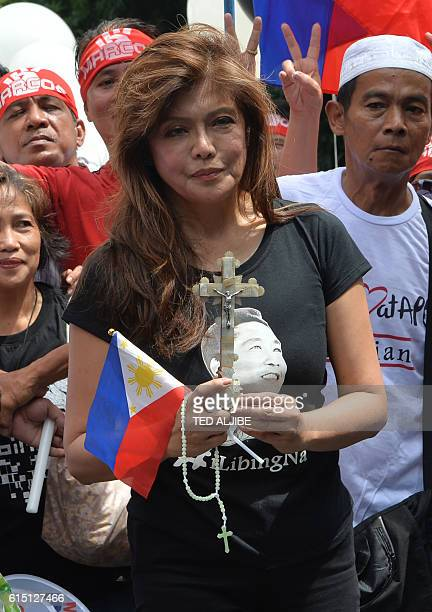 Imee Marcos daughter of the late dictator Ferdinand Marcos and governor of the family's northern stronghold of Ilocos Norte holds a crucifix and...