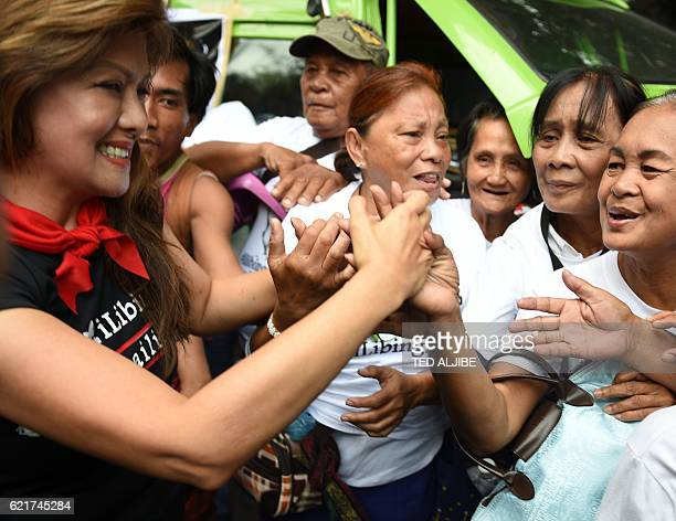 Imee Marcos daughter of the late Philippine dictator Ferdinand Marcos celebrates with supporters after hearing the news of the high court's decision...