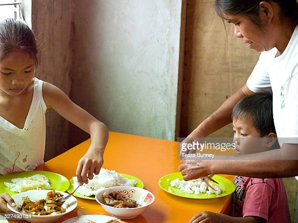 Imelda Esgana, fish vendor eating lunch at home with her two youngest children, Talisay, Bantayan Island, The Philippines. Every morning at 7 am...