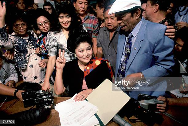 Imelda Marcos flashes a victory sign with daughter Imee and lawyer January 1 1992 in Manila Philippines