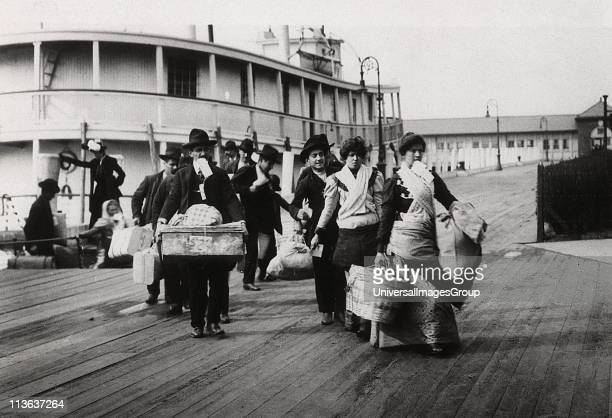 Imigrants to US landing at Ellis Island circa 1900 They head for the processing centre carrying paper with entry number which they hope will soon be...