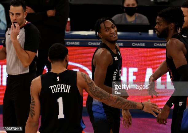 Immanuel Quickley of the New York Knicks is congratulated by teammates Obi Toppin and Nerlens Noel of the New York Knicks after Quickley scored a...