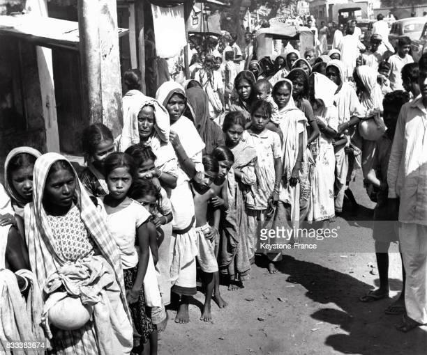 Immense file d'attente devant un magasin d'alimentation qui vend du riz à un tarif imposé par le gouvernement à Calcutta Inde en octobre 1963