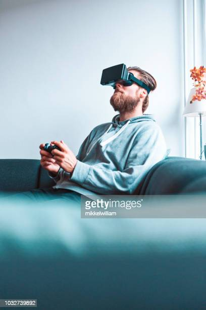 Immersive virtual reality experience for a man with VR glasses and handheld controller