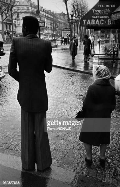 Immigré africain portant un pantalon pattes d'éléphant dans la rue à Paris circa 1970 France