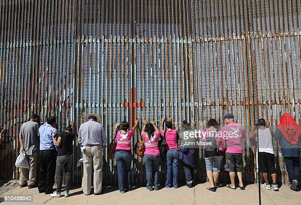 Immigrant activists pray at the USMexico border fence on September 25 2016 in Tijuana Mexico The US Border Patrol opens the park on the American side...