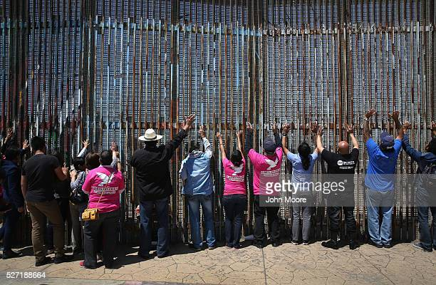 Immigrant advocacy groups pray at the USMexico border fence on May 1 2016 in Tijuana Mexico Mexicans on the Tijuana side can approach the border...