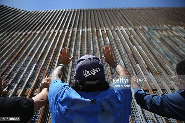 Immigrant advocacy members pray at the USMexico border fence on May 1 2016 in Tijuana Mexico Mexicans on the Tijuana side can approach the border...