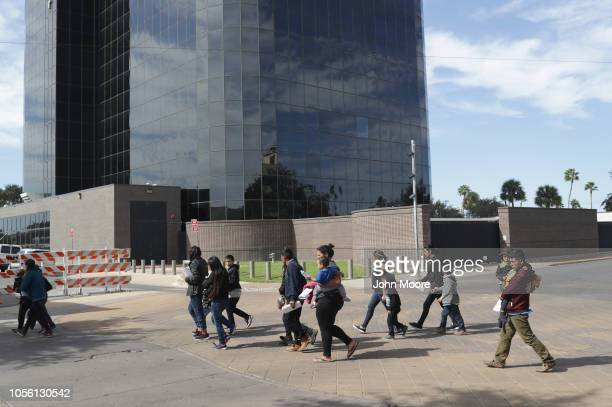 Immigrant asylum seekers walk past a US federal courthouse after being released by US Customs and Border Protection on November 1 2018 in McAllen...
