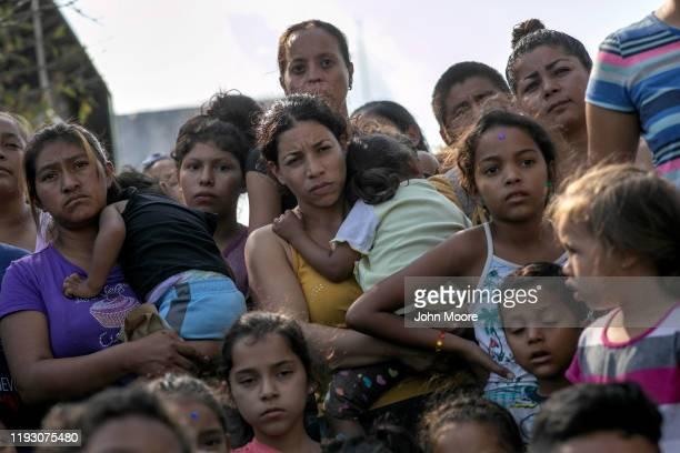 Immigrant children and mothers watch as the last bags of toys are distributed to other children following class at The Sidewalk School held at a...