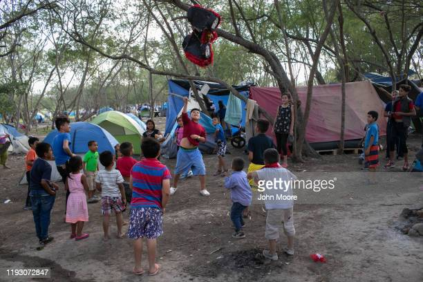 Immigrant children break a birthday pinata at a camp for asylum seekers on December 09 2019 in the border town of Matamoros Mexico More than 1000...